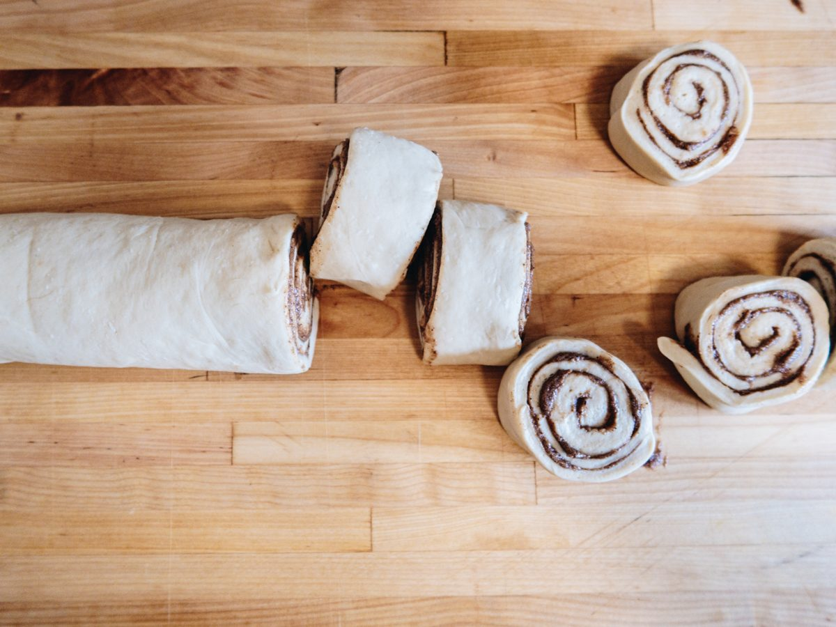 raw cinnamon roll log being sliced